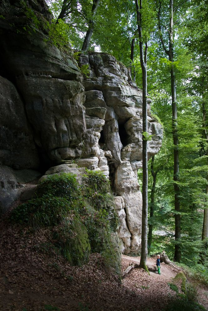 A tiny Jamie at large bizarre rock formations along the Mullerthal Trail in Luxembourg