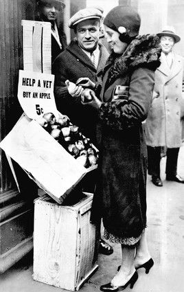 Great Depression, 1930  ( Photo courtesy Chicago Herald and Examiner )  A young woman buys an apple from an unemployed veteran on South Wells Street in 1930. With the onset of the Great Depression, unemployment hit 25 percent nationally.