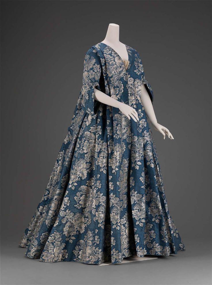 1730, Blue silk petticoat and overdress: loose fitting bodice and full skirt; short fitted sleeves with gathered asymmetrical cuffs; sack (Watteau) back; worn over trimmed corset. Museum of Fine Art, Boston, USA.