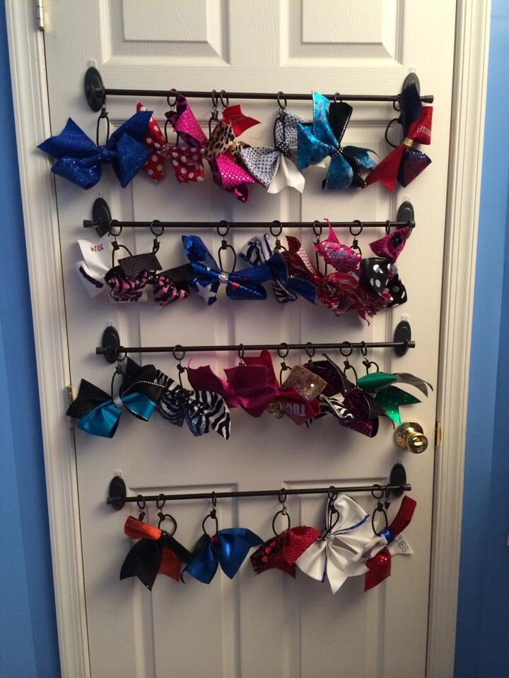 Cheer bow storage idea! Tension curtain rods held by Command hooks, with curtain clips. Bows clip onto each ring for easy on and off!