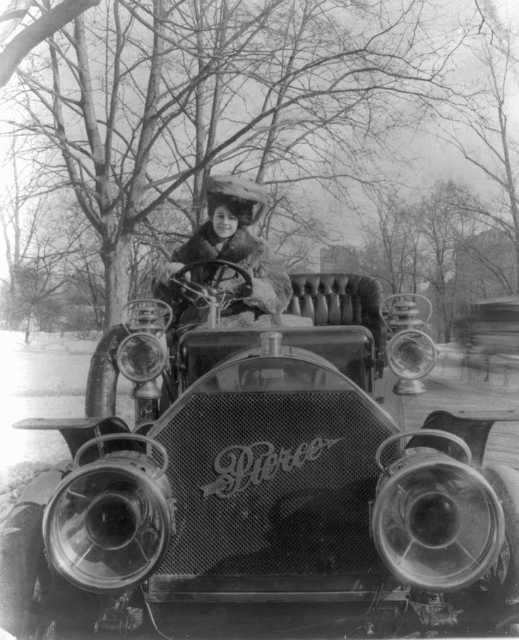 Woman in furs at wheel of open carriage Pierce-Arrow motor car, 1906