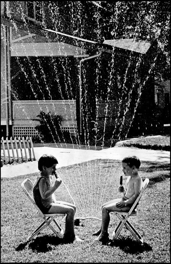 Vicki Vacek, 5 and Matt Johnson, 4 found the best way to beat the heat in 1968 – sitting under a lawn sprinkler while eating ice cream bars. ROBERT PASKACH/THE WORLD-HERALD