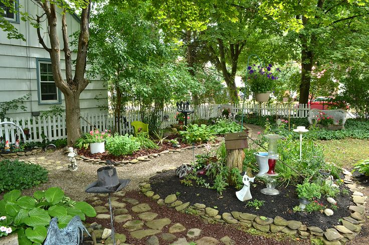 This backyard is too shady for grass to grow, so the gardener put in paths and garden beds.