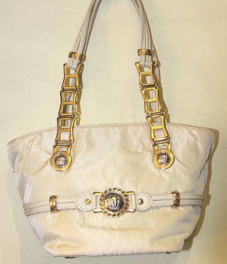 Elegante borsa firmata Versace, a due manici e chiusura a cerniera, in tela chiara, con rifiniture in vernice e meduse.