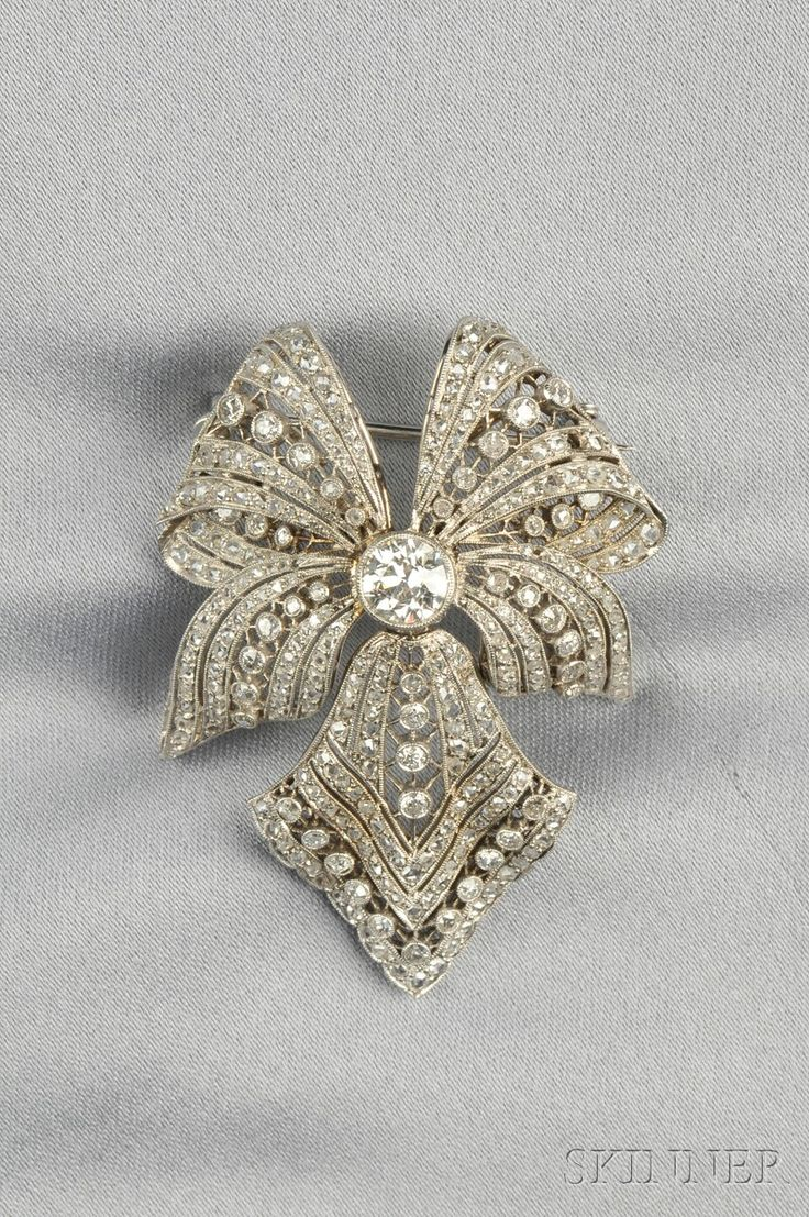 Platinum and Diamond Bow Brooch, set with an old European-cut diamond weighing approx. 0.95 cts., further set with old European- and rose-cut diamonds, millegrain accents, lg. 2 1/8 in. Edwardian or Edwardian style.