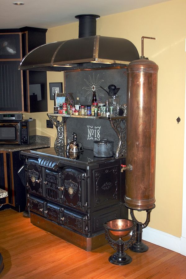 "A Steampunked Home.   ""The stove itself is another restoration form Erickson Stoves and has been fitted with a hi-end electric Miele halogen cooktop so there's no longer a need to stoke it with firewood.  Two electric ovens have been fit into the body of the stove as well."""