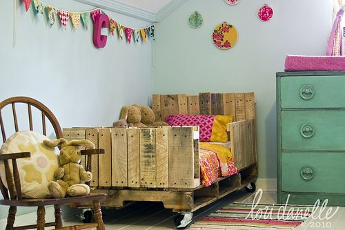 What a sweet, adorable girls room! Clever mom Lori Danelle used bolts and screws, 2-3 used shipping pallets and a set of caster wheels to make an eco friendly bed.  Sweet adorable shared girls room with painted floors.  The sisters bed. Who would've thought to use shipping pallets to make into a kids ...continue reading