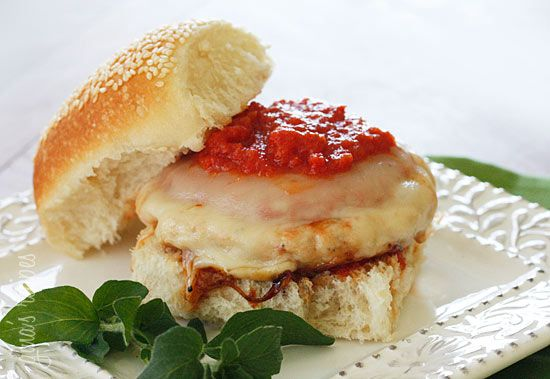 Chicken Parmigiana Burgers - A quick lunch or weeknight meal ready in less than 10 minutes your whole family will enjoy! Chicken burgers topped with pomodoro sauce and melted mozzarella on a hardy bun. Grill them or you cook them indoors in a skillet. Easy enough to adapt for one or a large group.