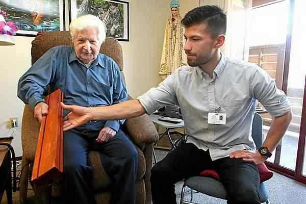Dominican Oaks resident Raymond Millard gets regular visits from Hospice volunteer Eric Flores. (Dan Coyro -- Santa Cruz Sentinel)