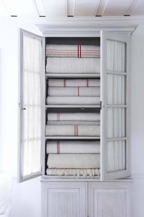 White armoire for bedlinens. Glazed doors are hung with gathered white voile.