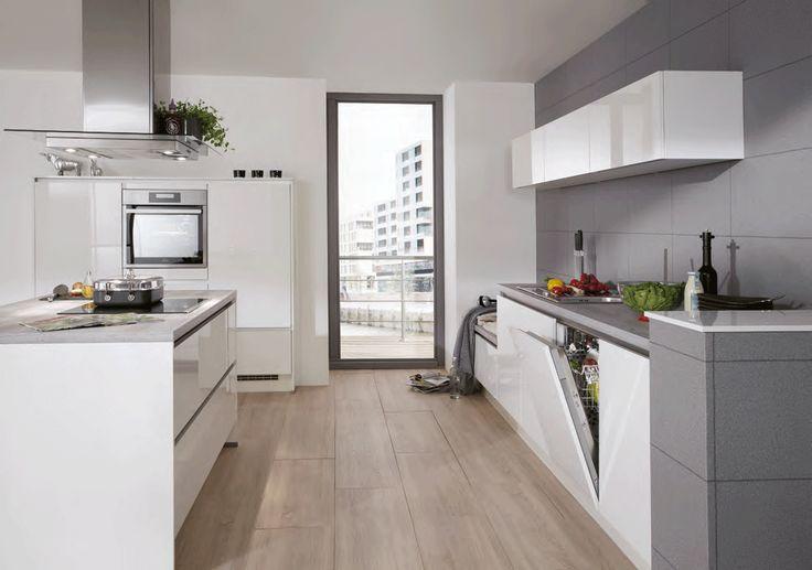 Grifflose Nobilia Lux Küche mit Kochinsellösung und grauer Arbeitsplatte zu hellbraunem Boden.