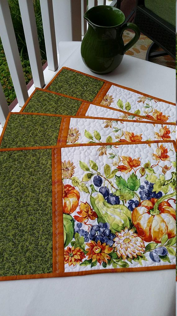 A set of four handmade quilted placemats featuring a cream print of fall pumpkins, gourds and flowers. A green vine print is separated from the cream print by a pumpkin orange flange. Backed in a light matching print then bound with a double fold of the pumpkin orange fabric which I attached by machine then turned and secured to the back by hand for a neat finish. Quilted on my home machine using a cream cotton thread. I used a decorative stitch of leaves on the orange flange, a puffy…
