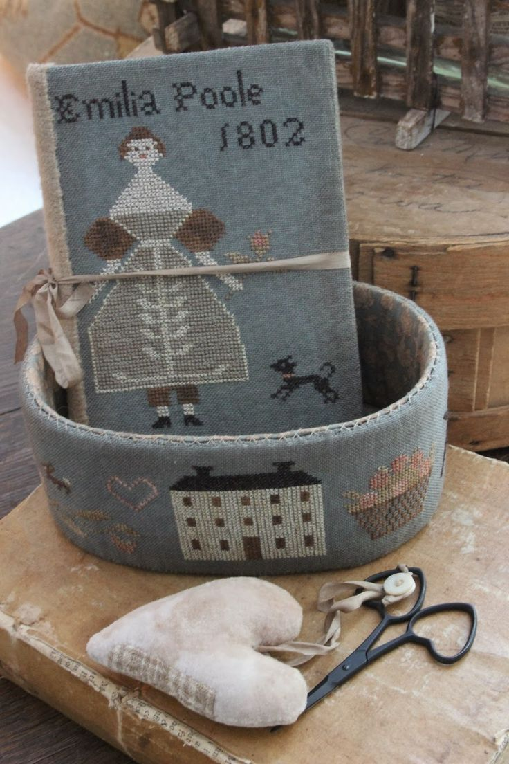 """Emilia Poole Basket,  Sewing Book & Heart Scissor Fob.  Picture 1 of 2.  Sizes:  5"""" x 7"""" x 3"""", Fob 2 3/4"""" x 3 1/2"""" & Book 5"""" x 7"""".  Oval paper mache box 5"""" x 7"""" x 3"""" high.  30 count Weeks Dye Works: Dolphin.  Gentle Arts threads: Chamomile, Roasted Marshmallow, Toasted Barley, Picnic Basket, Straw Bonnet, Espresso Bean & Woodrose.  Blackberry Primitives hand dyed velvet: Pearl."""