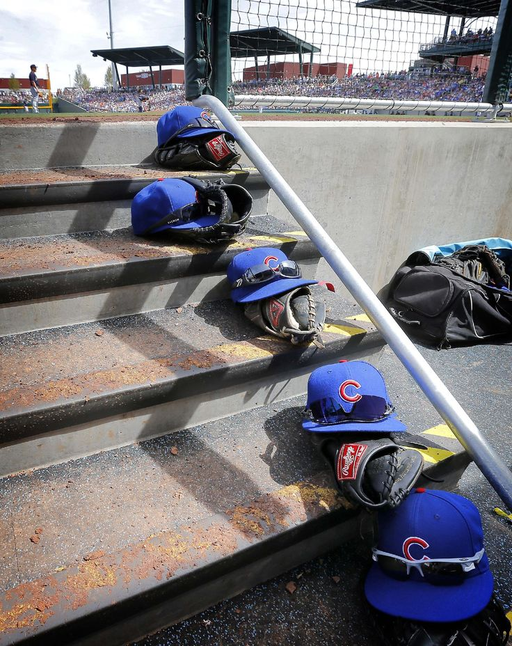 Ball caps and gloves line the steps of the Chicago Cubs' dugout during the second inning of the Cubs' spring training baseball game against the Seattle Mariners, Thursday, March 20, 2014, in Mesa, Ariz. (AP Photo/Matt York)