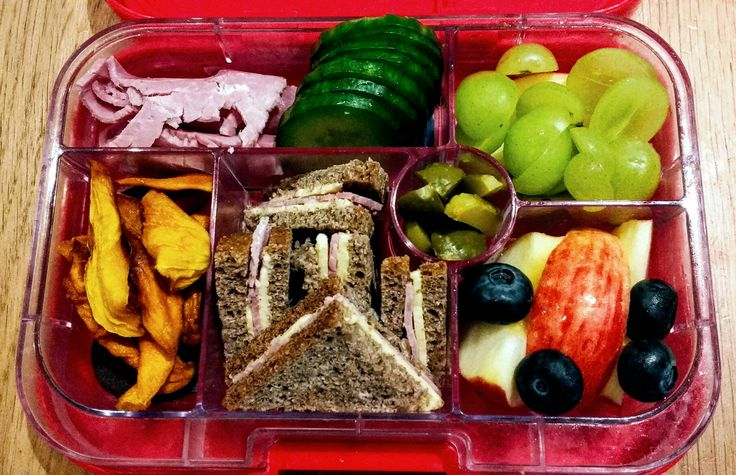 Toddler Lunchbox in a Yumbox: ham, cucumber slices, grapes, apple, blueberries, gherkins, dried mango and apricots plus sourdough rye ham sandwich.