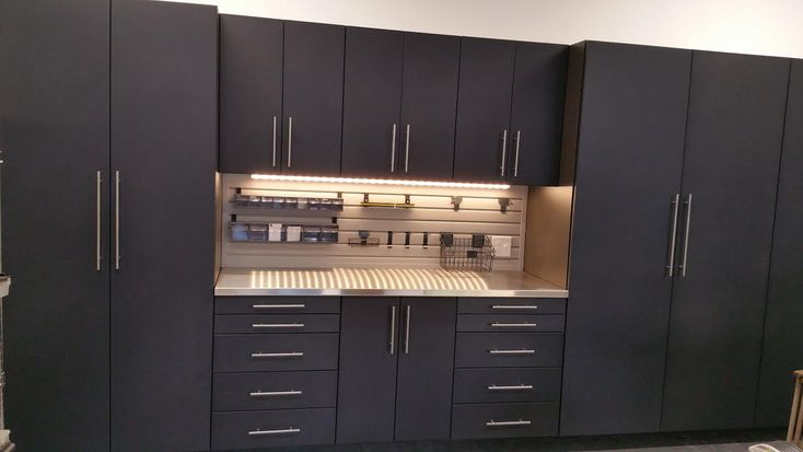 Custom black cabinets from Monkey Bar Storage, PVC slatwall above the workbench, and LED lights for tedious projects.