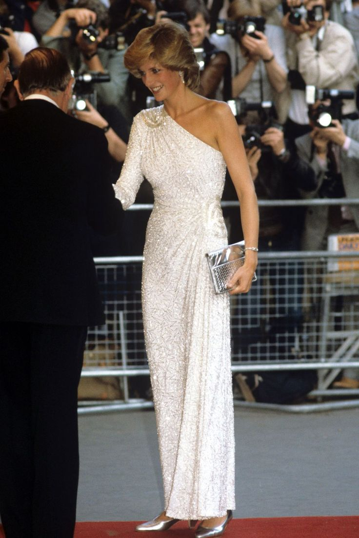 Princess Diana - Fashion and Style Icon | British Vogue: JUNE 1983 – Princess Diana attended the UK premiere of James Bond film Octopussy, which took place at Odeon Leicester Square, in the company of her husband, Prince Charles. For the glitzy occasion, the Princess wore a white asymmetric gown covered in silver bugle beads, teamed with a silver clutch bag and matching silver shoes.