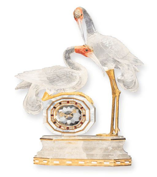 "Rock Crystal, Coral & Diamond Crane Clock by Boucheron. Paris. 2 hand-carved rock crystal cranes with coral heads enhanced by pavé-set diamonds, cabochon emerald eyes & 18K gold legs, with a marquetry mother-of-pearl clock with circular-cut diamond hands, within a ruby & diamond frame, all mounted on a rock crystal base. 10¼"" high, with French assay marks & maker's marks. Signed Boucheron. Sold in 2000 for $ 32,900. #rock_crystal #quartz #coral #Boucheron #clock #crane #decorative_arts"