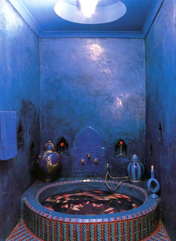 Bold blue tadelakt bathroom with a round bathtub tiled in