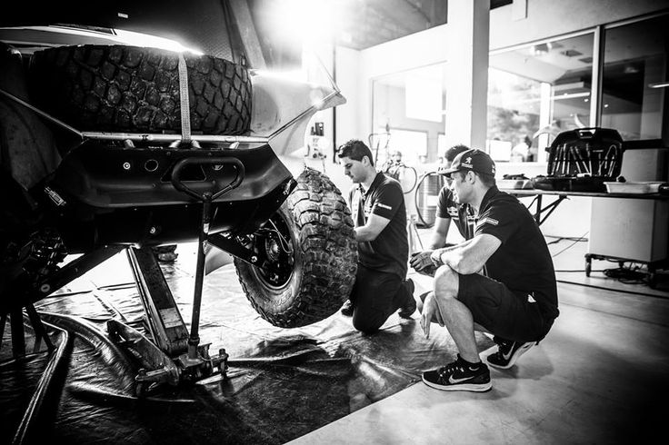Cyril Despres discusses in the workshop with the mechanics of the Peugeot 2008 DKR.