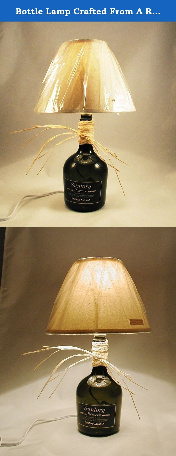 """Bottle Lamp Crafted From A Recycled Suntory Special Reserve Whisky Bottle. Shipping is included. Perfect lamp for a corner, counter top, end table, book shelf, bar or use as a night light in the bathroom. Crafted from a recycled Suntory Special Reserve whisky bottle. The bottle is darker green and the shade is off-white. Lamp is approximately 15"""" tall and approximately 11"""" wide (including the raffia). It burns up to a 60 watt bulb under the shade. The lamp shade and a 40 watt bulb are..."""