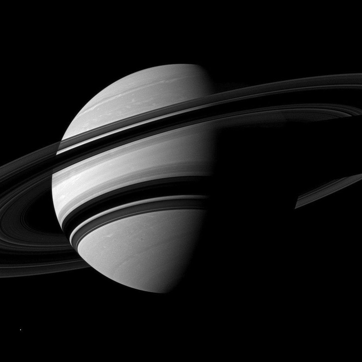 NASA's Cassini orbiter captured this view of Saturn on June 15, from a distance of about 1.8 million miles (2.9 million kilometers). The rings' shadow runs across the planet's sunlit side. The speck in the lower left corner is Enceladus, a 313-mile-wide (504-kilometer-wide) moon of Saturn.