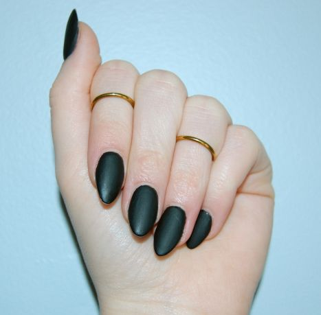 Black matte nails and midi rings.