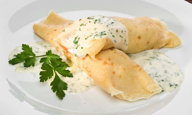 Crepes rellenos de endibias, salmón ahumado y champiñones, acompañados con una crema de perejil.