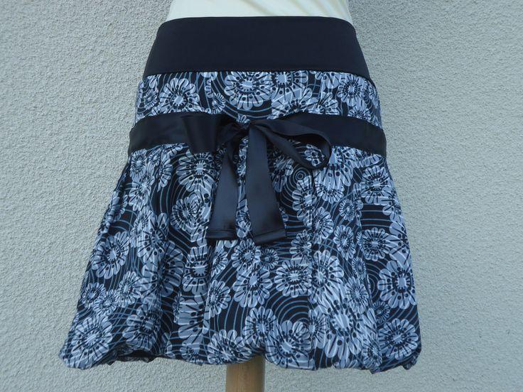 de dos Jolie jupe boule en coton noir avec des fleurs grise. Un ruban en satin noir de 4 cm est cousu sur le devant et se noue dans le dos. La ceinture de cette jupe est en lycra (jersey ou tissu extensible suivant disponibilité en magasin) pour s'adapter à toutes les morphologies.