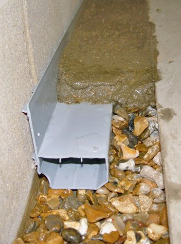 A French drain system installed along the perimeter of a basement floor.