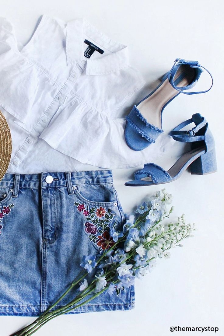 A pair of denim shoes featuring a crisscross ankle wrap with a buckle closure, a frayed open toe, and a block heel.