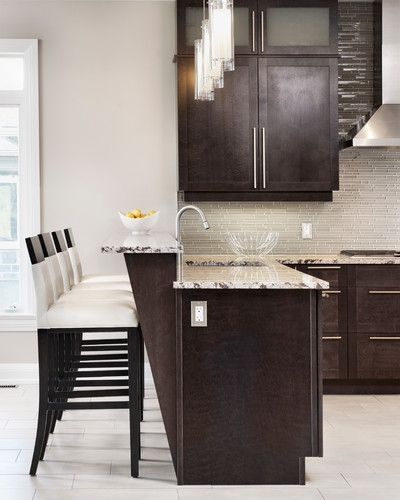 Dark contrasting cabinets with glass  brick set tile backsplash. Interesting detail with bar counter. Light walls and floor keep this kitchen from looking too heavy