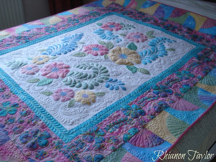 Appliqued flowers and feathers.  Free motion quilted.