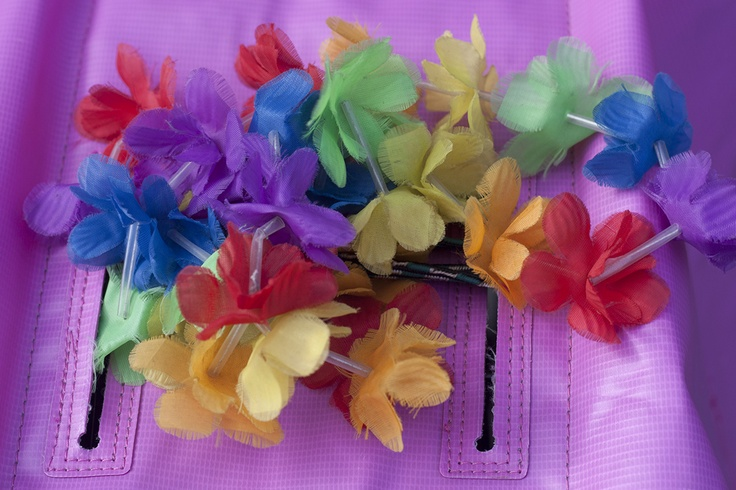 A colourful display of plastic flowers at the back of a bicycle.