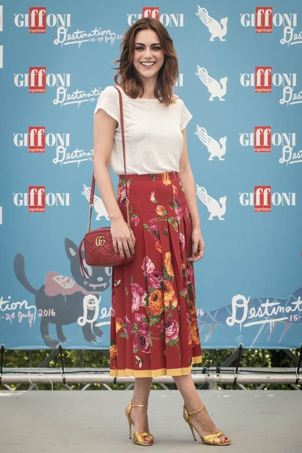 Italian actress Miriam Leone in a printed floral pleated skirt, gold sandals, and GG Marmont shoulder bag from the Fall Winter 2016 collection at the Giffoni Film Festival 2016.