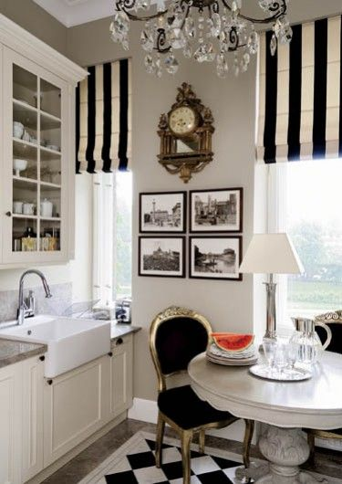 Black and white Roman shades, art, white cabinetry, small table