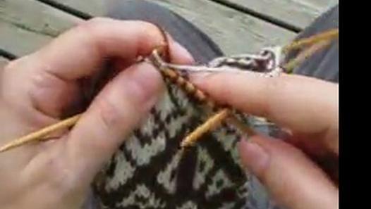 Démonstration d'une technique de jacquard qui utilise les deux mains: une pour chaque couleur, ainsi que la façon d'attacher la couleur non-utilisée quand on ne l'utilise pas pendant plusieurs mailles.