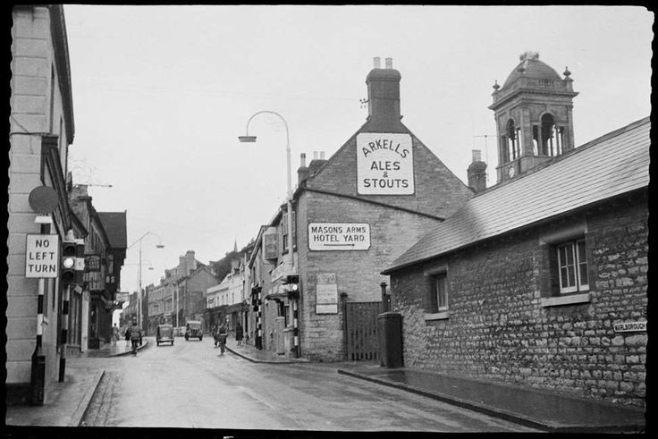 High Street, Old Town, Swindon, Wiltshire. With the exception of the former Town Hall tower, visible behind the Mason's Arms, few of the buildings seen here remain today. Photographed by Andor Gomme in 1957. © Historic England Archive