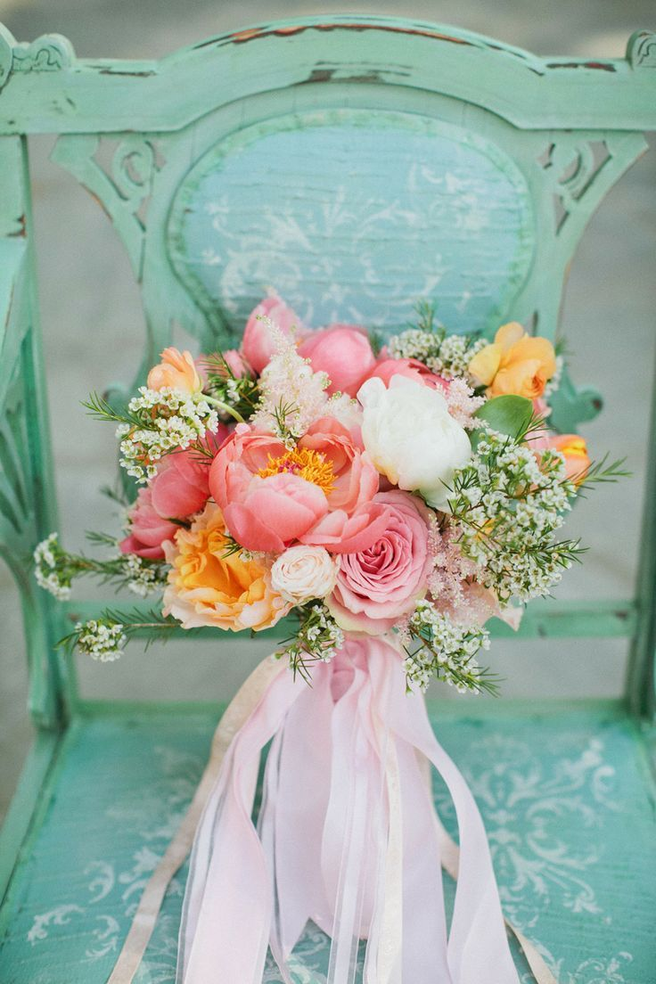 Spring peonies, peach caraluna roses, wax flower and ranunculus. With some blue muscari or delphinium, this could look stunning.