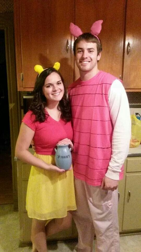 Adult Winnie the pooh and piglet halloween couple costume. Red shirt, yellow skirt, yellow pompom ears. Pink stripe shirt, pig ears.