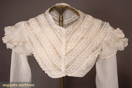 Hussar-styled summer blouse, 1815-1825, White tabby cotton trimmed with couched white cotton braid and bobbin lace insertions, high neckline, front closure, bodice constructed of diagonal bands of lace and self-fabric trimmed with braid in loop design, long sleeves with puffed cap decorated with raised gathered muslin puffs, single fabric covered button at lace and braid cuff