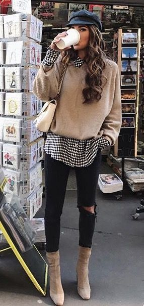 Beige sweater over black and white checked shirt with black jeans.