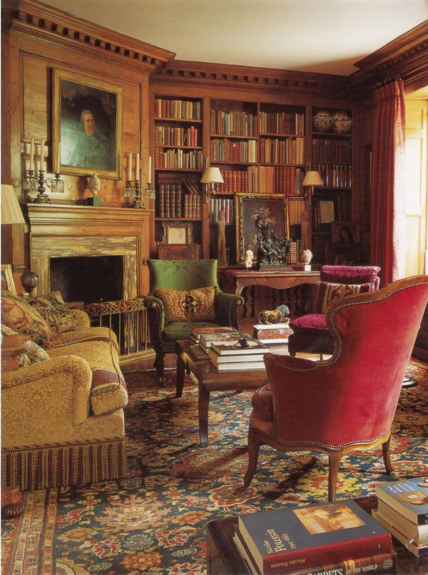 This Victorian-style library is cozy and inviting, with rich wood bookcases and paneling, jewel-toned, comfortable furnishings and a fireplace to make a warm spot for curling up with a good book.