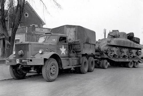 "Heavy 12-ton Diamond T 981 truck hauls away a damaged M4A1 (75) ""Sherman"" tank for repair in Haguenau, France. During the war, this type of trucks were supplied to the USSR under the Lend-Lease program"