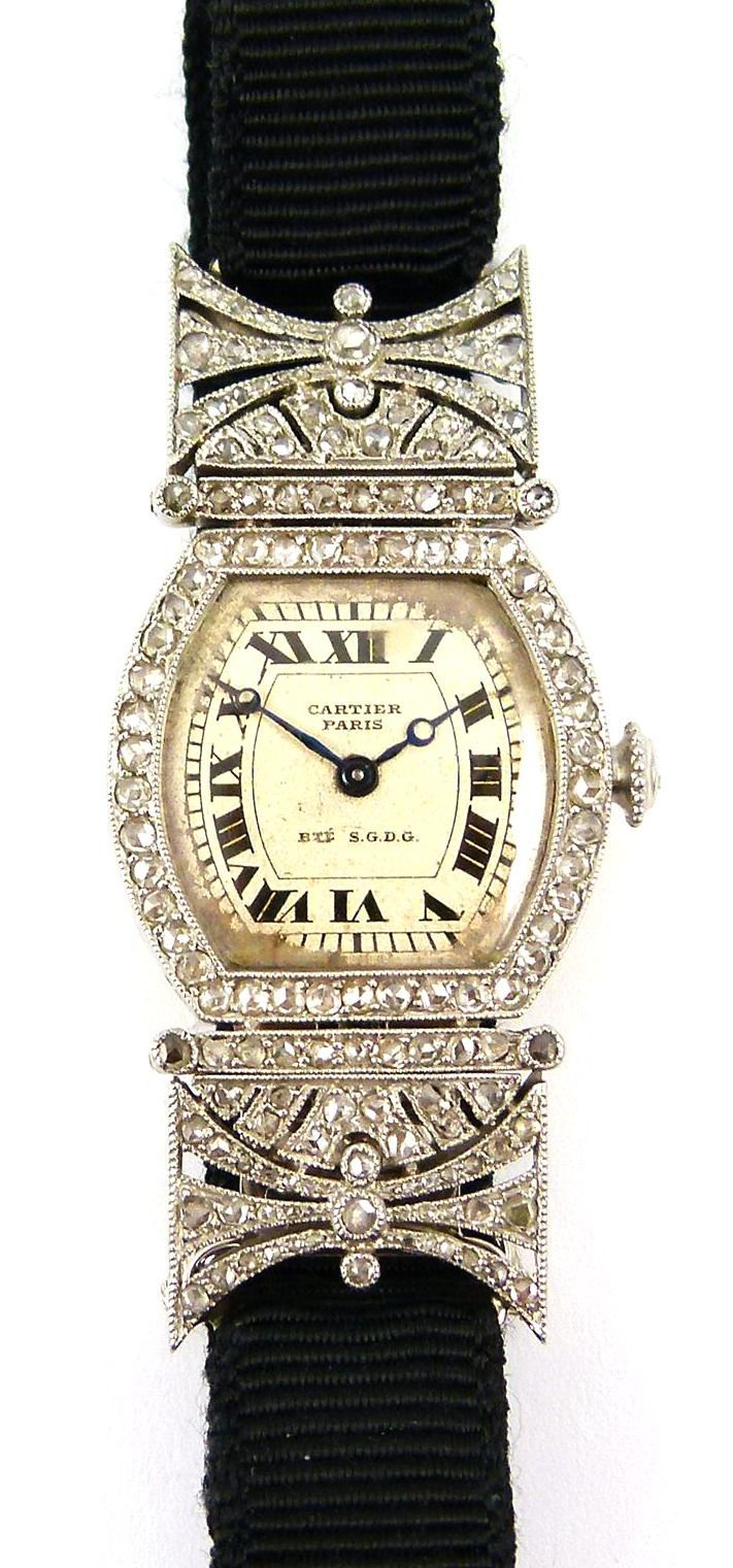 Cartier ~ Circa 1920 Art Deco diamond set lady's turtle wristwatch Paris: the tortoise shaped silvered dial with black Roman numerals, rose diamond set bezel and winder, the shaped rectangular shoulders pierced and millegrain set with rose diamonds, mounted in platinum, the case back in gold.