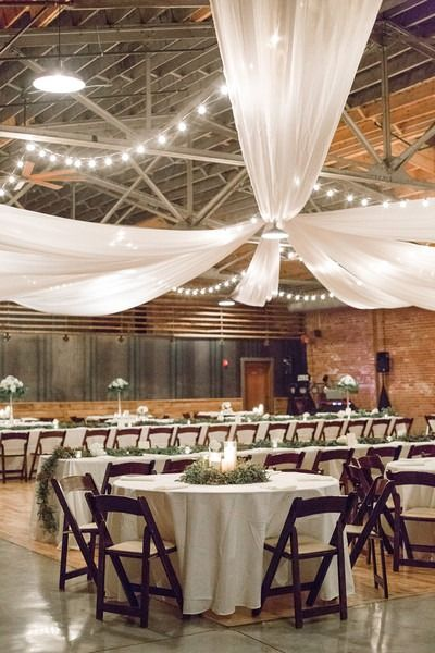 Winter wedding reception decor idea - white, draped fabric with twinkle lights, white banquet tables and greenery wreath centerpiece {JOPHOTO}