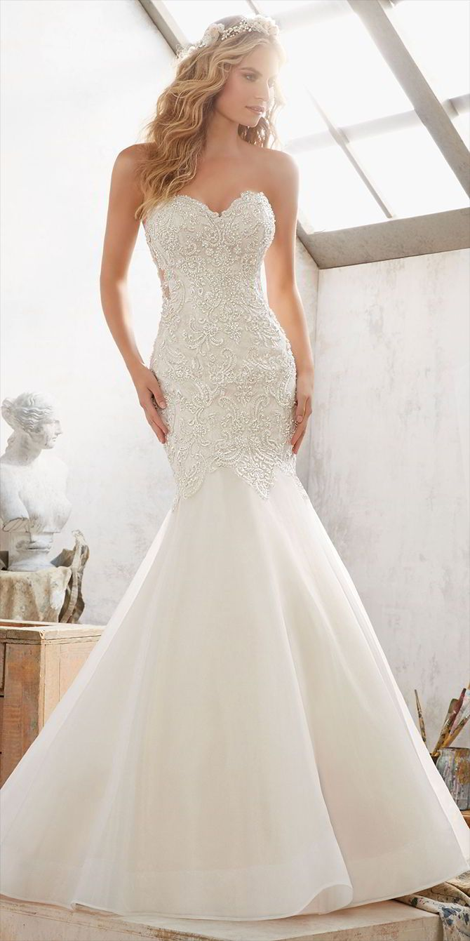 Crystal Beaded Embroidery Over Chantilly Lace Adorns the Bodice of This Dreamy Fit & Flare Wedding Dress. Featuring a Romantic Sweetheart Neckline and Organza Skirt. Covered Button Details Accent the Corset Style Illusion Back.