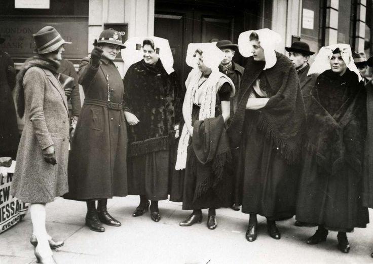 Klederdracht : Nederlandse vrouwen in Zeeuwse klederdracht, op bezoek in Londen voor een folkloristisch dansfestival in de royal Albert hall, krijgen aanwijzingen van een vrouwelijke politieagent / Bobby. Engeland 1930 #Zeeland #ZuidBeveland #protestant #katholiek