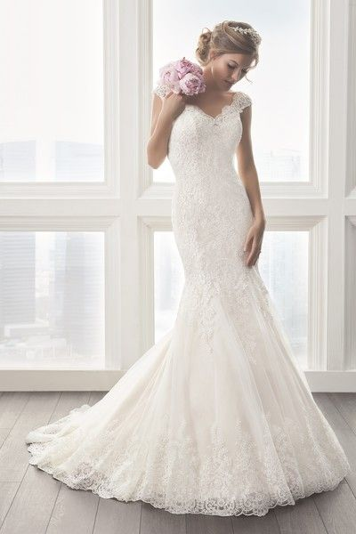 <strong class='info-row'>Christina Wu</strong> <div class='info-row description'>15623   Beautiful lace appliqués sprinkled with sequins trail down this trumpet dress providing a beautiful, romantic pattern. Lace-covered cap sleeves open up to a low back. Border lace that matches the body wraps around the hem. Covered buttons are placed over the back zipper.</div> <div class='row info-row text-center'> <div class='col-xs-6 col-xs-offset-3'> <a class='image-caption-view-website'…