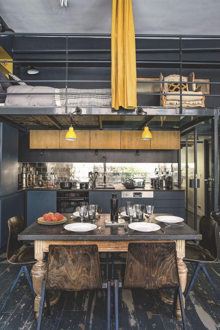 """Sous la mezzanine en partie transparente, la cuisine s'ouvre sur la pièce de vie. Association des bleus, """"Hague Blue"""" et """"Black Blue"""", Farrow&Ball, l'un presque noir, l'autre presque canard à la lumière du jour, en accord avec les pieds des chaises chinées comme la table en Belgique. Parquet belge également, The Colour Republic. Lampes moutarde, Lampe Gras DWC éditions, rideaux et linge de lit, AM.PM"""